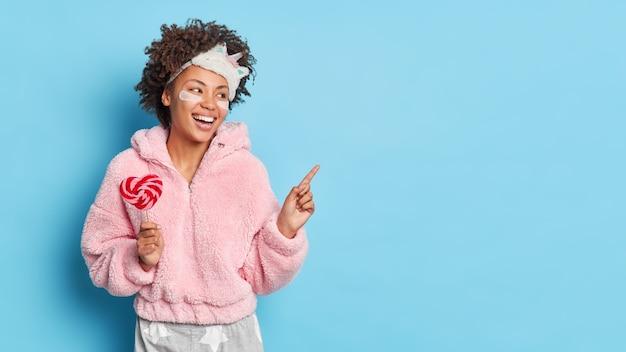 La mujer feliz señala en el espacio de la copia se siente energizada por la mañana después de que un buen sueño indica a un lado y anuncia el producto para una gran siesta sostiene el lollipop usa pijama aislado sobre una pared azul