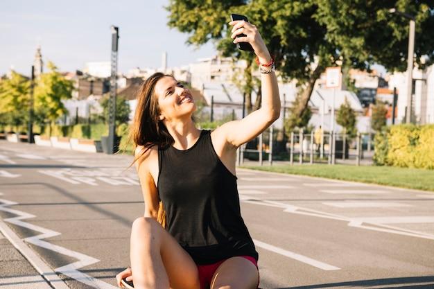 Mujer feliz sentada en patineta tomando selfie con celular