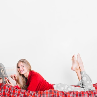 Mujer feliz con smartphone acostado en cama
