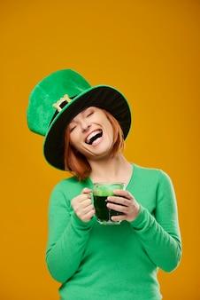 Mujer feliz con sombrero de duende bebiendo cerveza