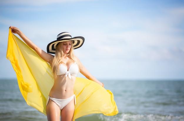 Mujer feliz sonriendo y divirtiéndose en la playa. retrato de verano de joven hermosa en la playa con una bufanda amarilla y sombrero.