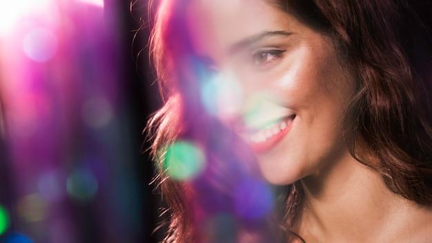 Mujer feliz sonriendo y efecto de destellos borrosos