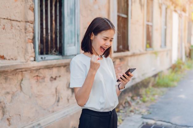 Mujer de feliz sonriendo y sosteniendo teléfono inteligente con asombrado para el éxito