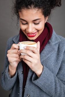 Mujer feliz sonriente en abrigo con taza de café