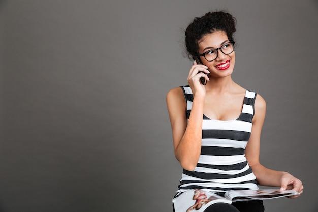 Mujer feliz sonriente que habla en el teléfono móvil mientras que sostiene la revista