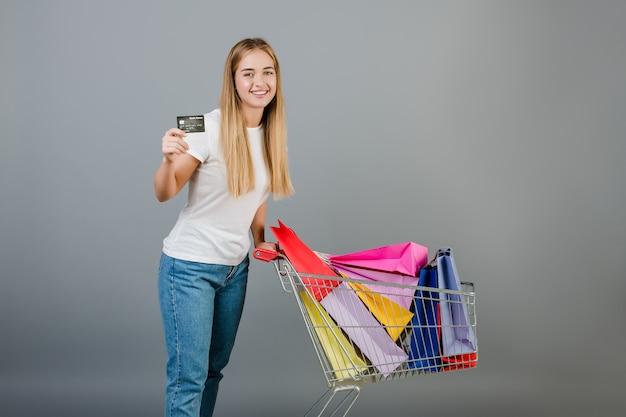 Mujer feliz sonriente con tarjeta de crédito y carretilla de mano con coloridas bolsas de compras aisladas sobre gris