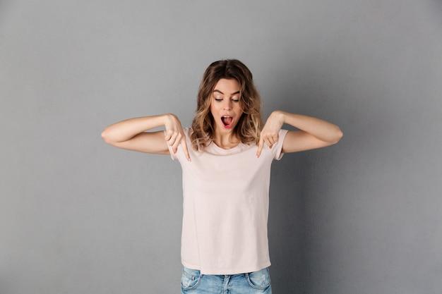 Mujer feliz sorprendida en camiseta apuntando y mirando hacia abajo con la boca abierta