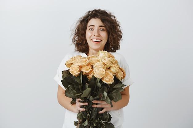 Mujer feliz sorprendida recibe hermoso ramo de flores, entrega de floristería