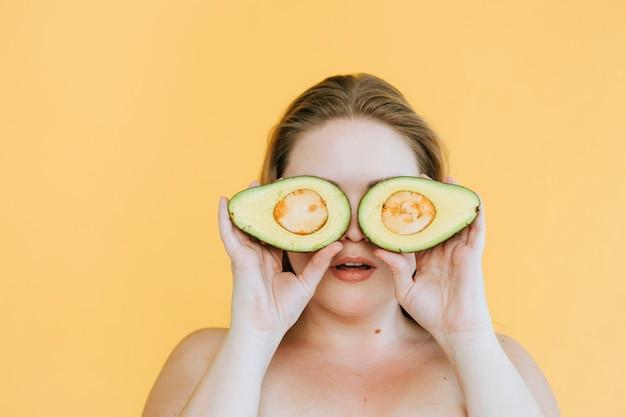Mujer feliz sosteniendo aguacates recién cortados sobre sus ojos