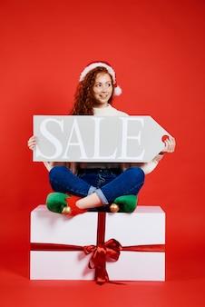 Mujer feliz sosteniendo banner de venta de navidad