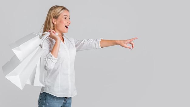 Mujer feliz sosteniendo bolsas de la compra y apuntando a una posible venta en la tienda