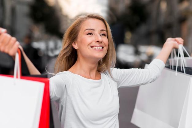 Mujer feliz sosteniendo bolsas de la compra después de la sesión de compras de venta
