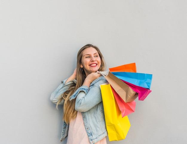 Mujer feliz sosteniendo bolsas de compras detrás de la espalda