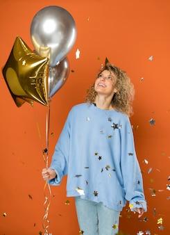 Mujer feliz sosteniendo globos