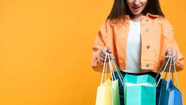 Mujer feliz sosteniendo y mirando dentro de bolsas de la compra con espacio de copia