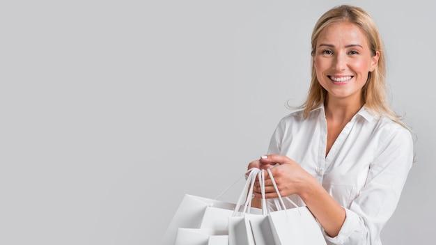 Mujer feliz sosteniendo un montón de bolsas de la compra.