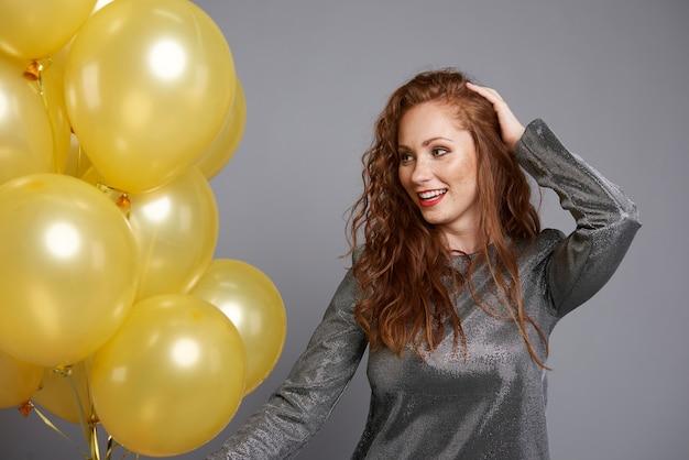 Mujer feliz sosteniendo un montón de globos
