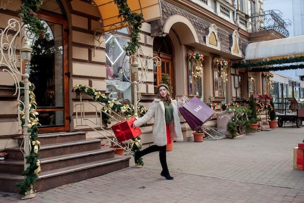 La mujer feliz sostiene la caja de regalo en sus manos y sonríe saliendo de la tienda. hermosa niña feliz posando con regalos de navidad. preparación de año nuevo.