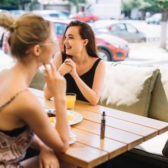 Mujer feliz con su amiga desayunando juntos