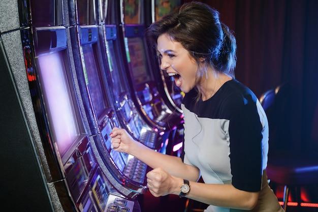 La mujer está feliz de su victoria en máquinas tragamonedas