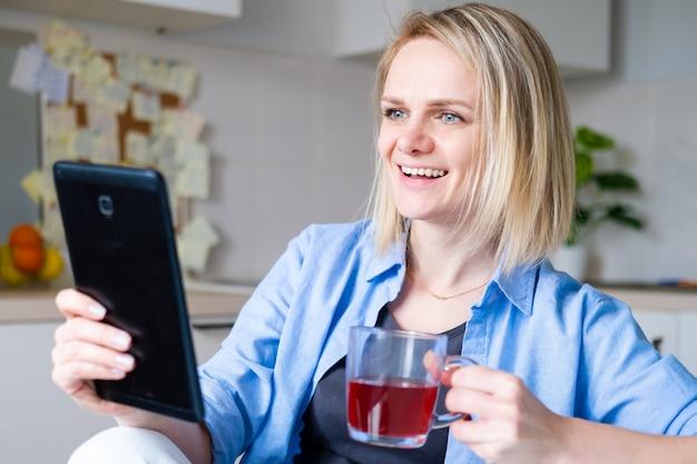 Mujer feliz con tableta digital para videollamadas amigos y padres, niña sonriente sentada en casa cocina diversión saludo en línea por computadora cámara web haciendo videollamada
