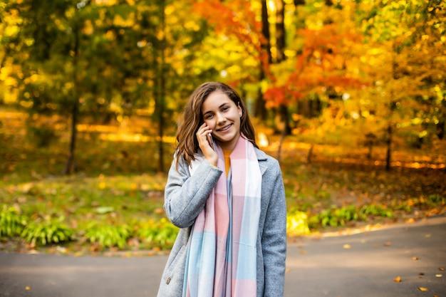 Mujer feliz por teléfono celular en el parque otoño