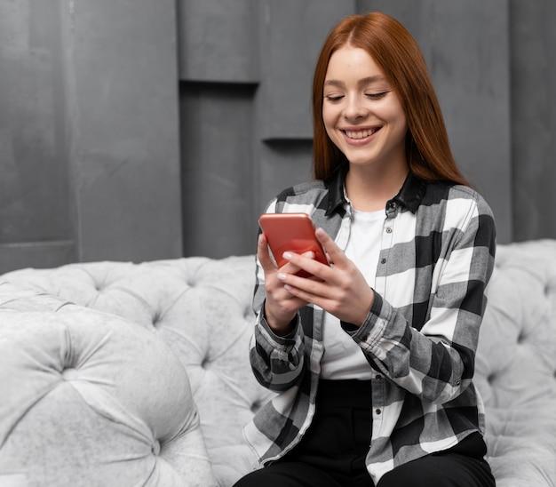 Mujer feliz en el teléfono inteligente en el interior