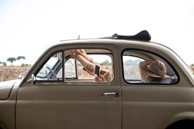 Mujer feliz con teléfono móvil dentro de coche retro
