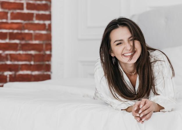 Mujer feliz de tiro completo en la cama