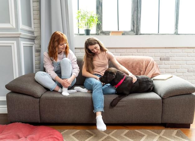 Mujer feliz de tiro completo y perro en el sofá
