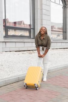 Mujer feliz de tiro largo caminando en la ciudad
