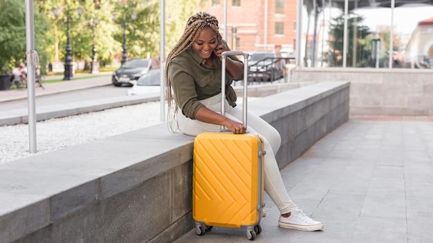 Mujer feliz de tiro largo mirando hacia abajo en su equipaje