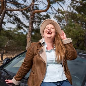 Mujer feliz de tiro medio con coche