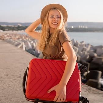 Mujer feliz de tiro medio con equipaje