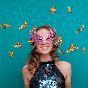 Mujer feliz con tiro medio de máscara rosa