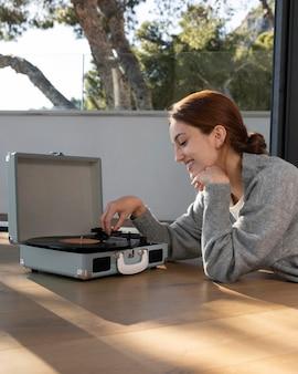 Mujer feliz de tiro medio con música