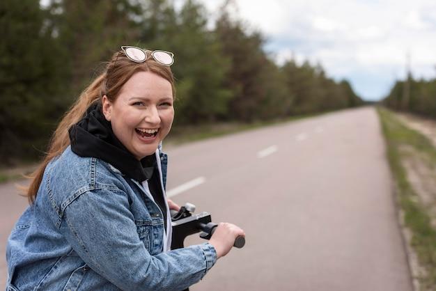 Mujer feliz de tiro medio con scooter