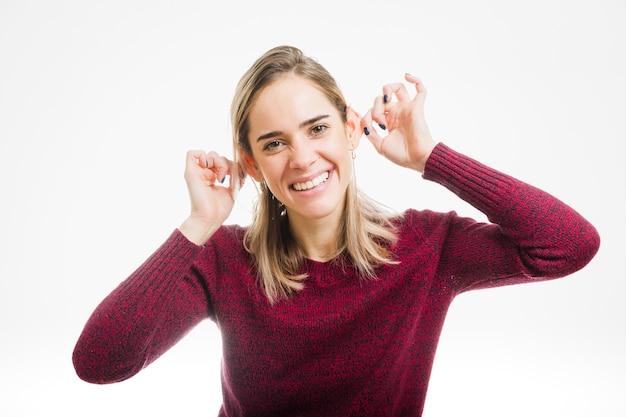 Mujer feliz tocando sus orejas