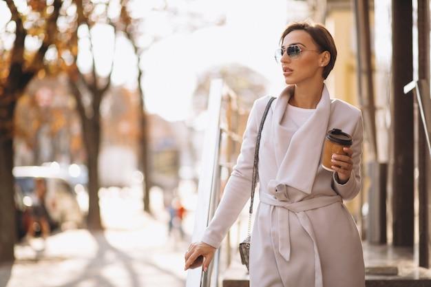 Mujer feliz, tomando café en la calle.