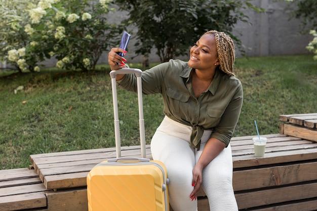 Mujer feliz tomando un selfie junto a su equipaje
