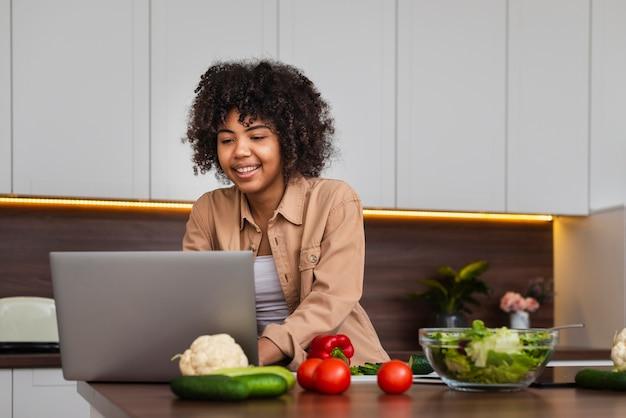 Mujer feliz trabajando en la computadora portátil en la cocina