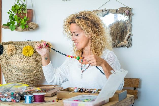 Mujer feliz en el trabajo a domicilio con perlas y cordones produciendo joyas más baratas