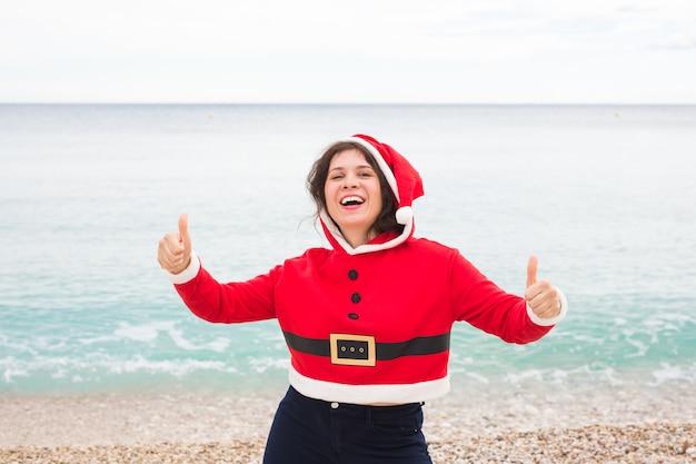 Mujer feliz en traje de santa claus en la playa mostrando los pulgares para arriba
