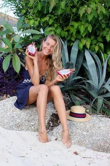 Mujer feliz tranquila caucásica en vestido azul sostiene fruta del dragón en la playa tropical