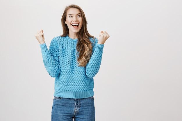 Mujer feliz triunfando, puño bomba y decir sí