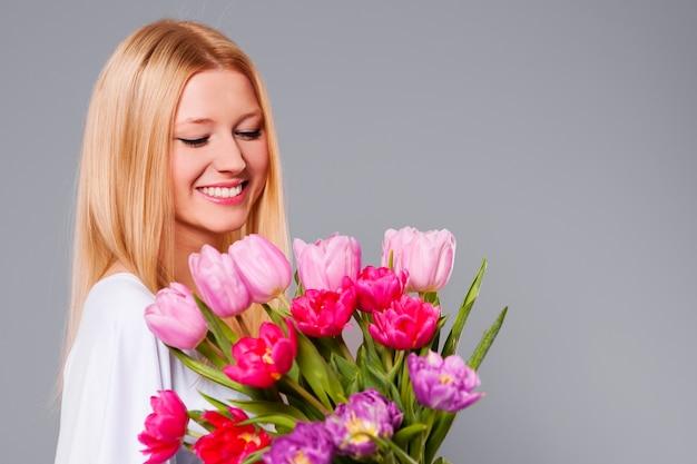 Mujer feliz con tulipanes rosados y púrpuras