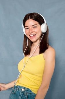 Mujer feliz usando audífonos tiro medio