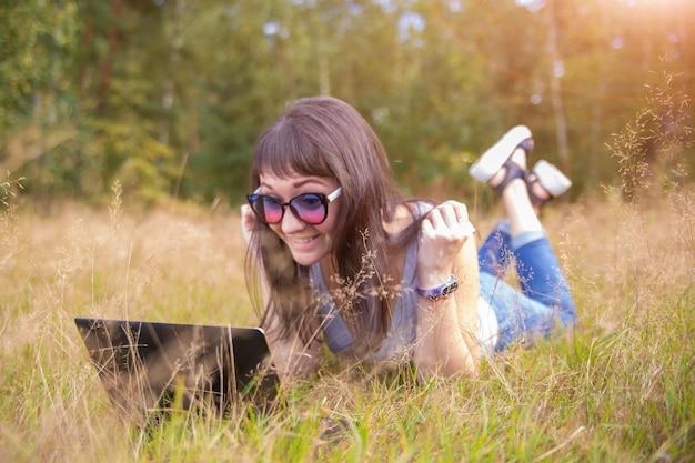 Mujer feliz usando la computadora portátil en el campo feliz freelancer de trabajo remoto bajo el sol