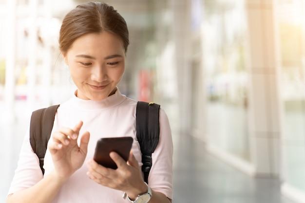 Mujer feliz usando teléfono inteligente en la ciudad