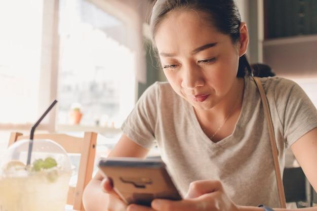 Mujer feliz está utilizando smartphone en el café café.